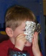 Child looking through piece of foil
