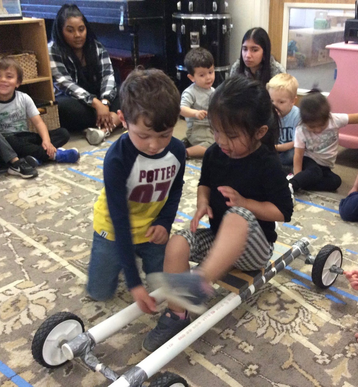 Students try the big car model in circle time.