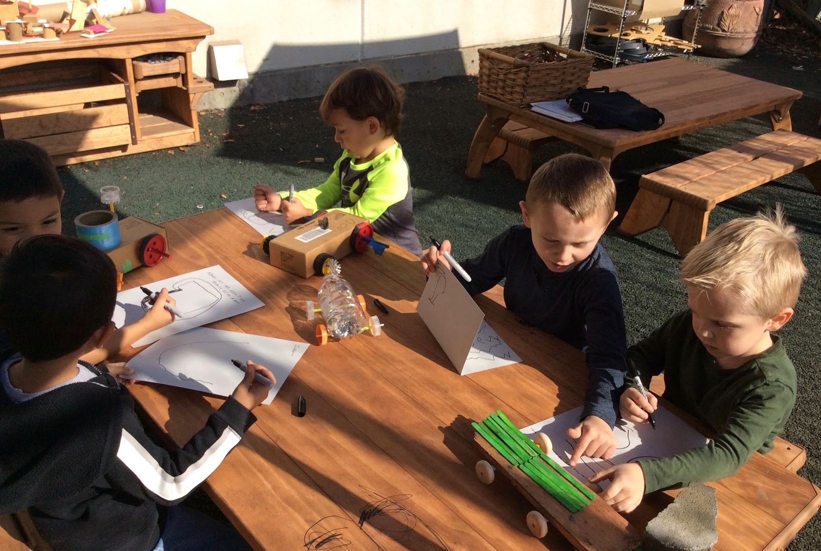 """Children are in a Maker Space designing their """"really fast"""" cars."""