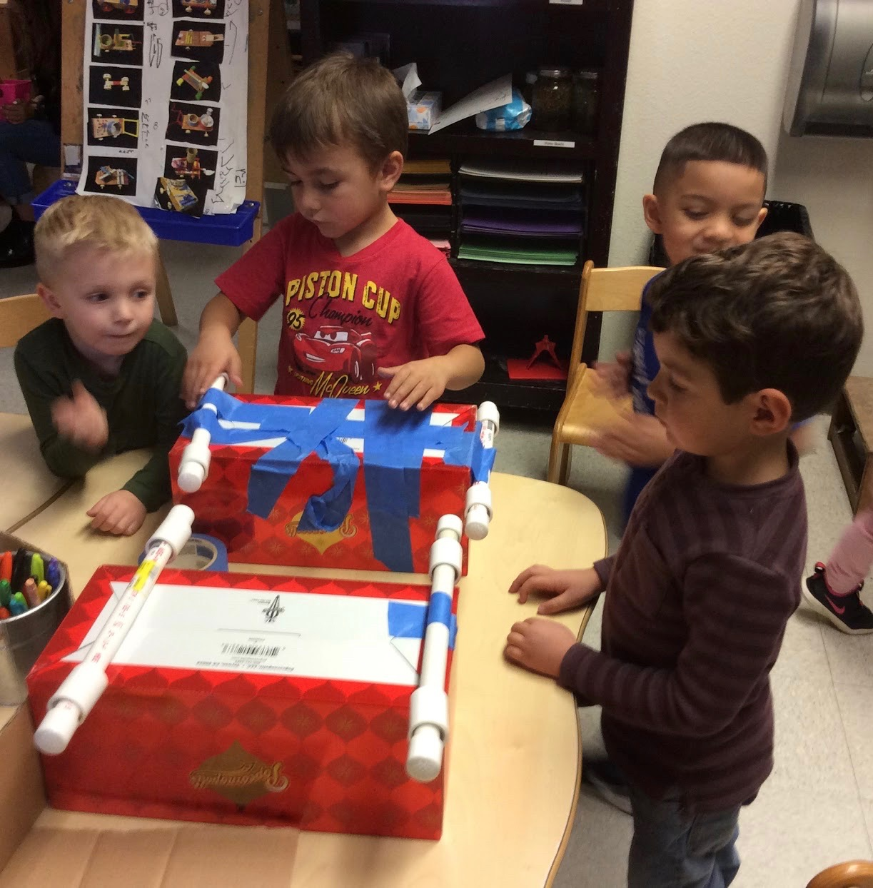 Children constructing two new cars with similar dimensions for further testing of their hypotheses.