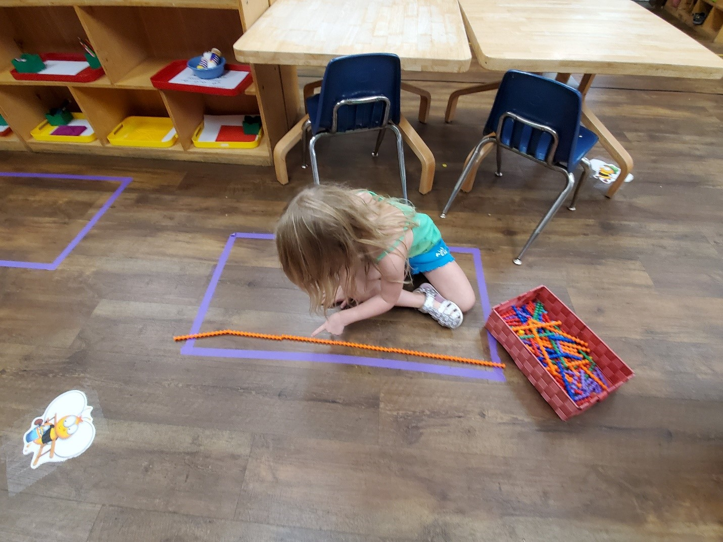 A learner uses manipulatives as a non-standard measurement tool.